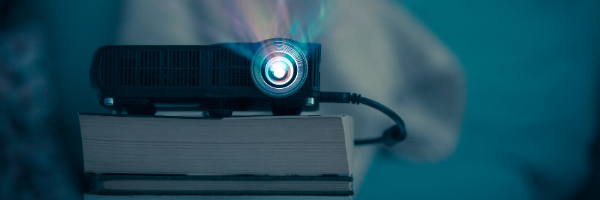 black projector on stack of books