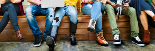 people sitting on bench using electronics