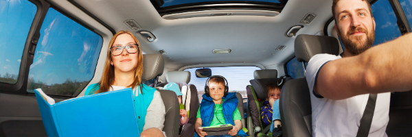 family of five in car with book and tablet