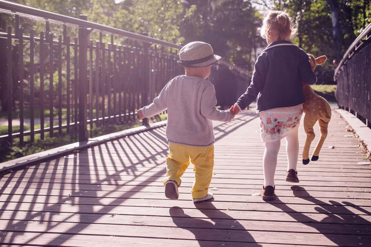 two young kids walking on bridge