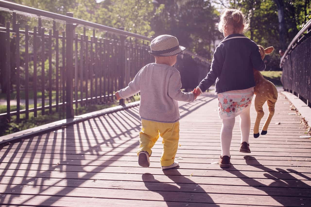 two young kids walking on bridge
