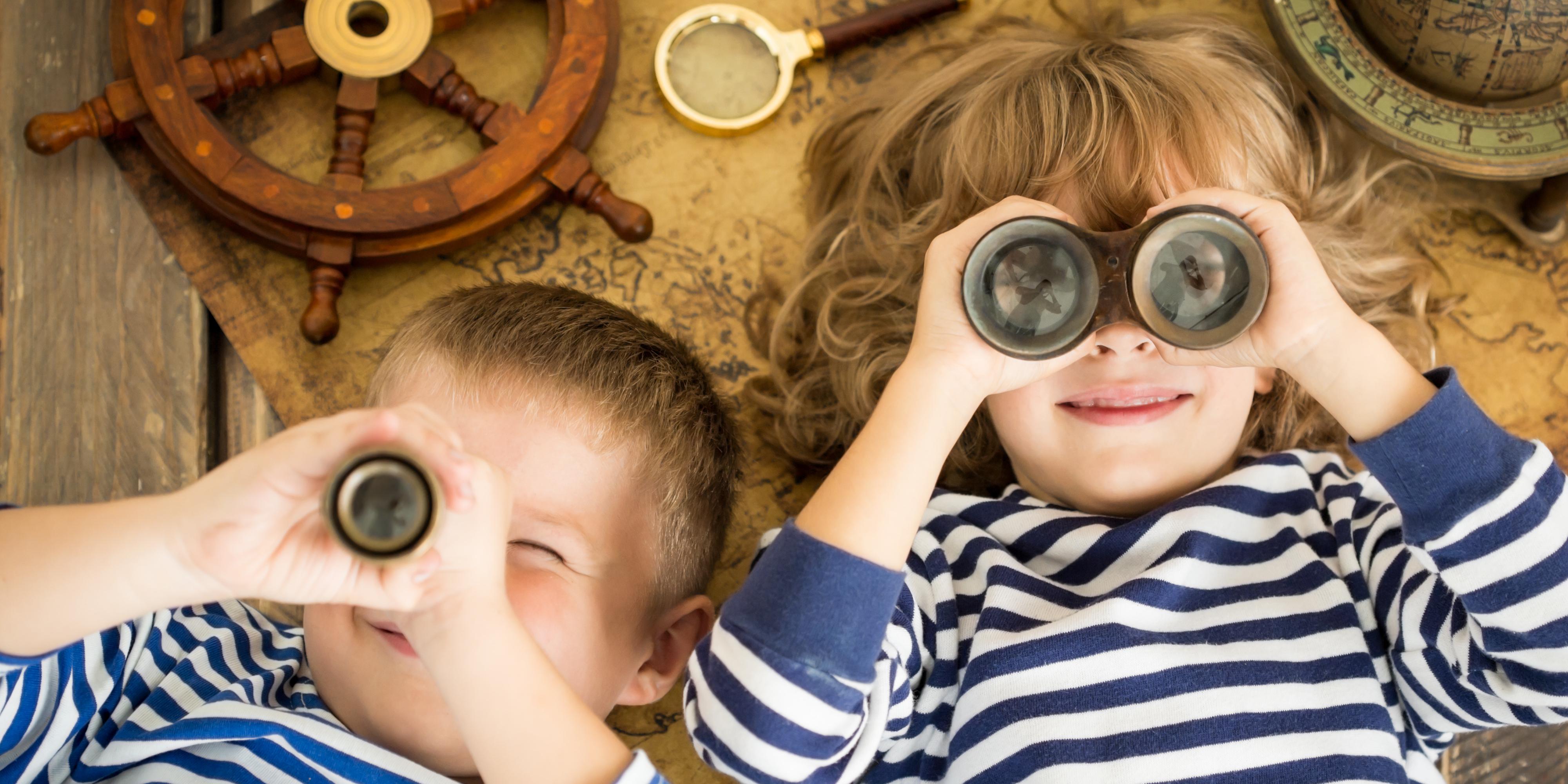two kids wearing stripes looking out binoculars