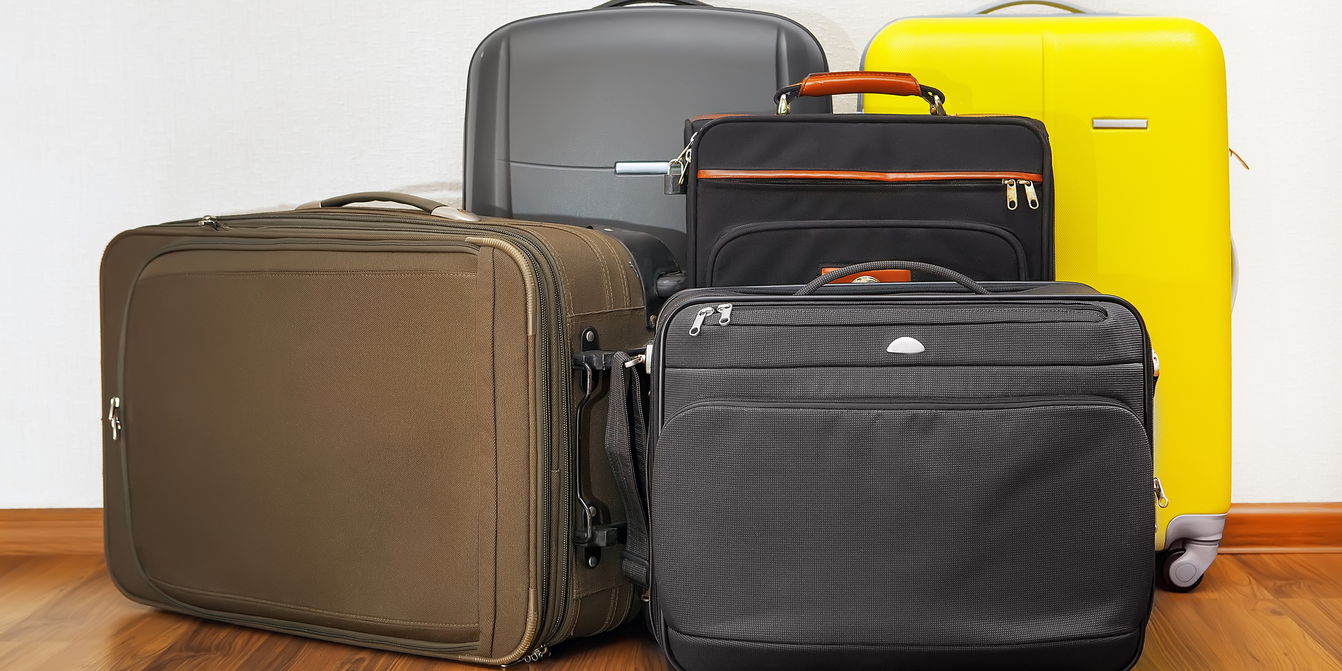 group of luggage bags in front of wall