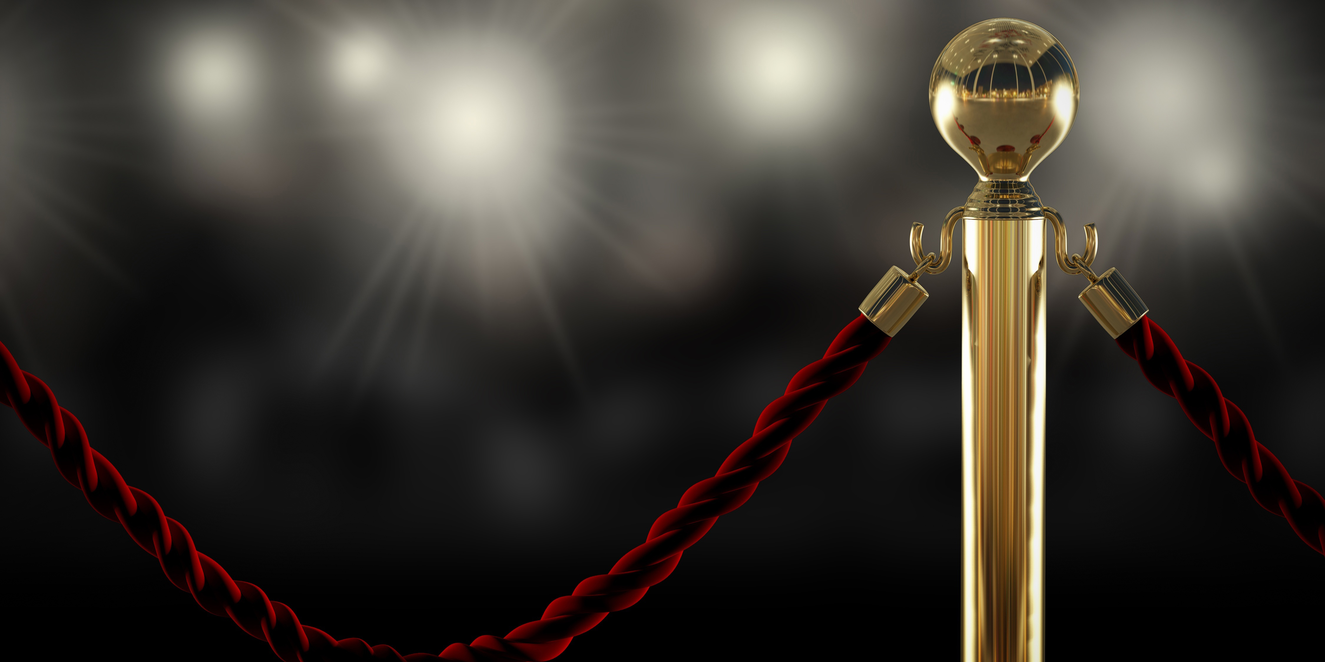 Red rope attached to gold pole with lights in the background